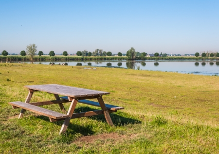 Wooden picnic table near a lake in a Dutch nature area  Stockfoto