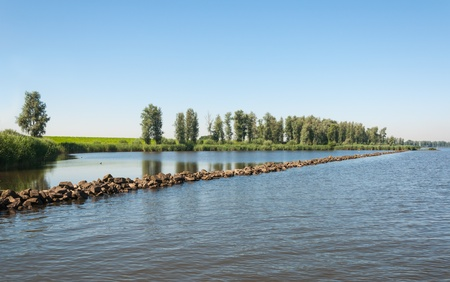 Colorful landscape in the Netherlands with a river and a straight dam of basalt stones  photo
