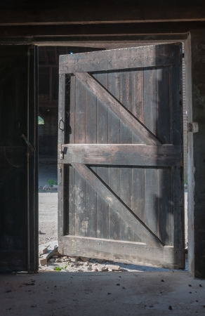 The old wooden door of the abandoned barn is open