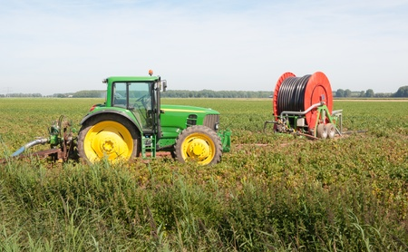 irrigation equipment: Colorful tractor with attached pump and a water reel for irrigation in a rural landscape
