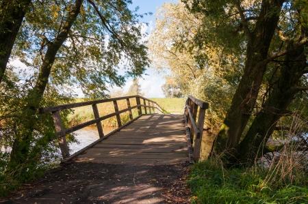 Holzbrücke über einen kleinen Fluss in einer ländlichen Landschaft im Herbst