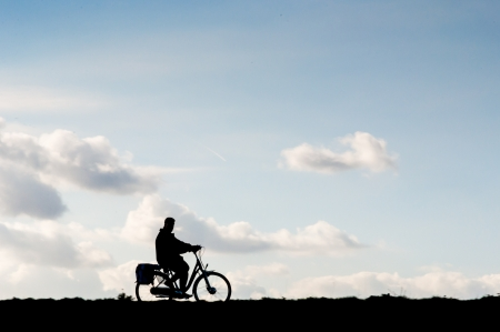 one wheel bike: One bicyclist is riding alone on a dike in the Netherlands
