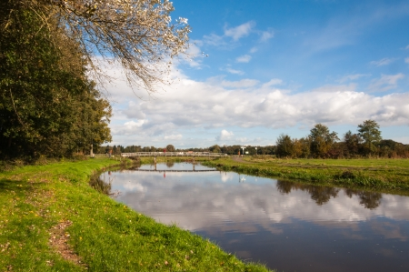Rural landscape in the Netherlands with a small reflecting river, a bridge, trees and some clouds at the blue sky Stock Photo - 15808098