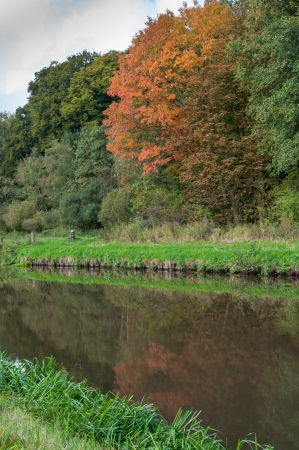 windless: Beautiful fall colors and reflections at the mirror smooth surface of a stream on a sunny and windless day  Stock Photo