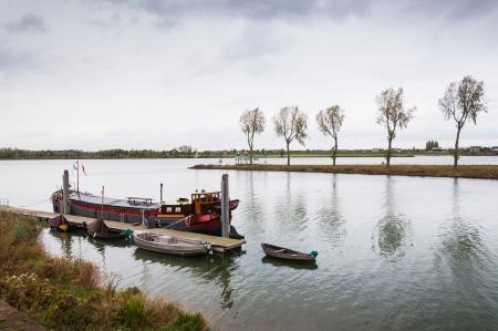 Vrachtschip afgemeerd aan een houten steiger in een rivier in Nederland Stockfoto