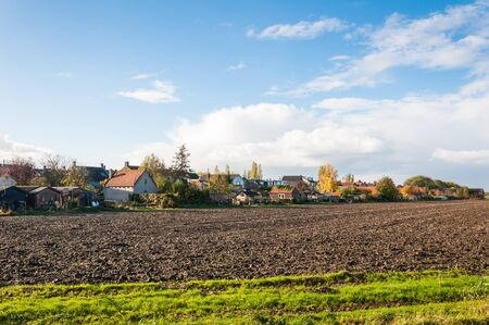 A small village in the Netherlands at the edge of a freshly plowed field. photo