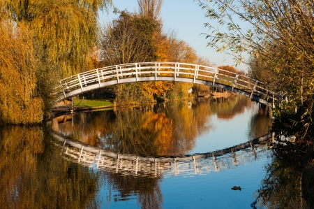 Curved wooden bridge over a small canal in a Dutch autumn landscape. photo