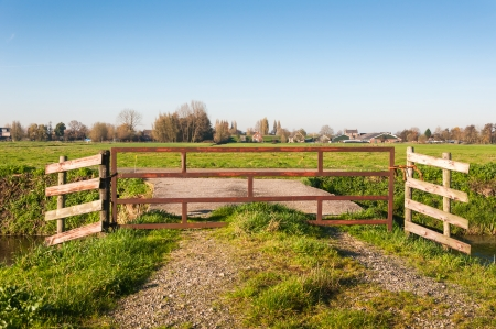 Polder landscape in the Netherlands with a small village in the background and a fence in the foreground. photo
