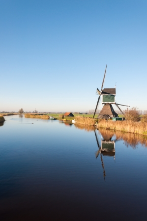 Polder landscape in autumn with a typical windmill and its reflection in a mirror smooth water surface. photo
