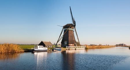 Side view of a windmill on a small river in a polder in the Netherlands. It is autumn now. photo