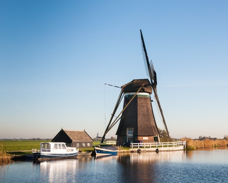 Side view of a windmill on a small river in a polder in the Netherlands. It is autumn now. Stock Photo - 16409126