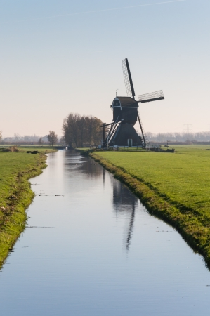Side view of a windmill at a polder ditch in the Netherlands. It is autumn now. photo