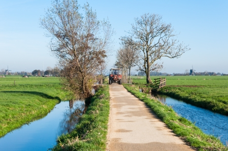 An old red tractor rides over the full width of a narrow polder road in the Netherlands. photo