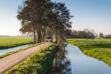An old red tractor with a small trailer rides over the full width of a narrow polder road between ditches in the Netherlands. Stock Photo - 16409153