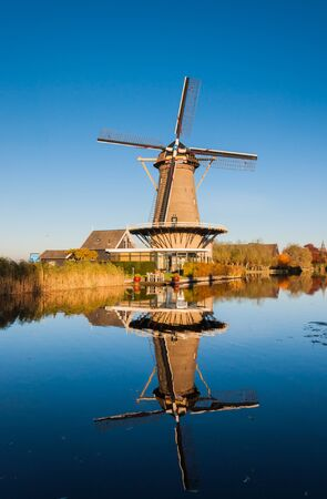 Historic windmill in the Netherlands reflected in a mirror smooth water surface of the river. photo