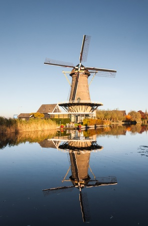 Historic windmill in the Netherlands reflected in a mirror smooth water surface of the river. Stock Photo - 16409179