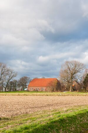 Threatening storm clouds above an old farm in a rural landcape with bare trees in the Netherlands. Stock Photo - 16605309