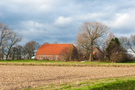 Threatening storm clouds above an old farm in a rural landcape with bare trees in the Netherlands.
