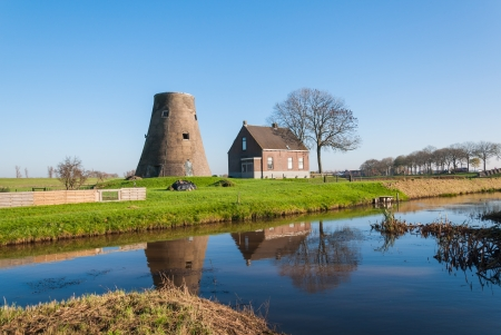 Dutch truncated windmill, a house and a bare tree perfectly reflected in the mirror smooth water surface.