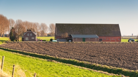Arable farm and barn in the background o a fresh plowed field  Stock Photo - 16704808