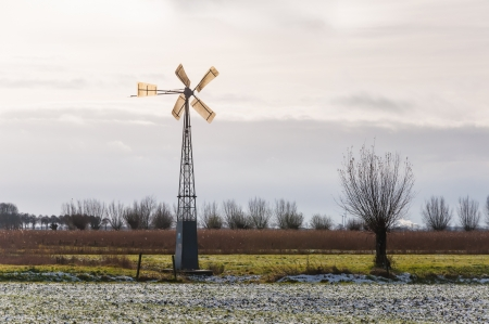 Wintry landscape with some snow on the field and an old metal windmill. photo