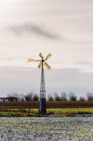 Wintry landscape with some snow on the field and an old metal windmill. Stock Photo - 16749995