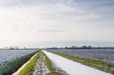 Rural winter landscape with plowed fields, a ditch and a countryroad covered with untouched snow. photo