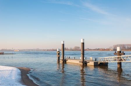 Jetty and pontoon along tall bollards in a Dutch river with snow on the sand of the shore. Stock Photo - 16877186