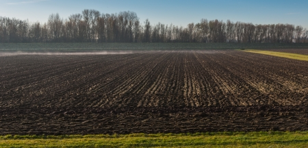 Rural landscape in autumn with still some morning mist above the plowed field. photo