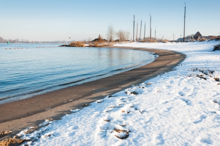 curvature: Curvature in a Dutch river with snow on the sandy riverside.
