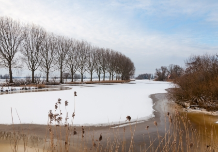 Dutch river covered with snow and ice in winter