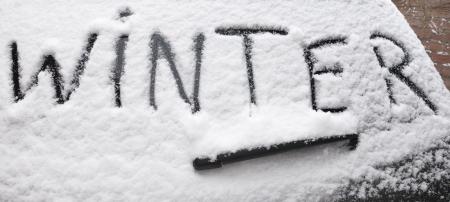 Op de achterruit van een auto het woord Winter is geschreven in de vers gevallen sneeuw. Stockfoto