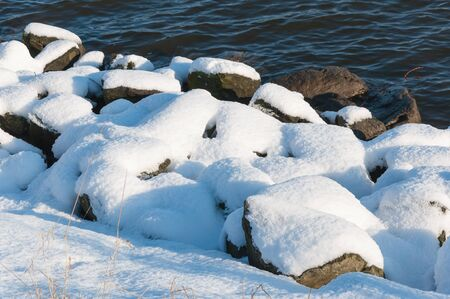 Snowy rocks along the still rippling water of the river in wintertime. photo