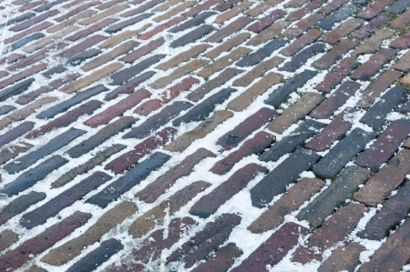 Closeup of snowy old bricks in varied colors in an historic Dutch street. Stock Photo - 17406098