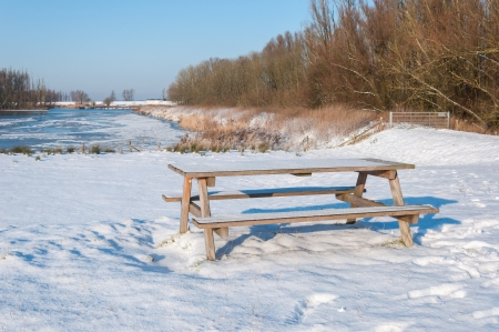 Wooden picnic furniture covered with a freshly fallen layer of snow  photo