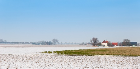 Partially snow covered fields and a white farmhouse with a red tiled roof in a Dutch agricultural area. photo