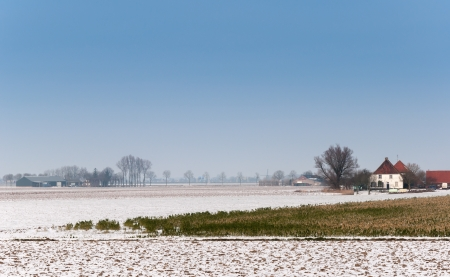 covered fields: Partially snow covered fields and a white farm with a red tiled roof in an agricultural area in the Netherlands.