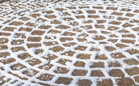 Circulaire sneeuw cijfers over de sierbestrating van het terras. Stockfoto