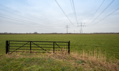 Iron fence and high voltage lines and towers in a rural area In the Netherlands. photo