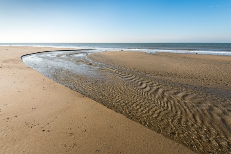 Flowing water at low tide on the Dutch North Sea coast photo