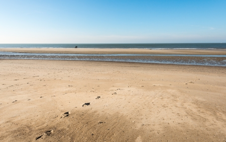 Picture of the beach on a sunny day in spring and in the distance the silhouette of a lone rider on a horse. photo