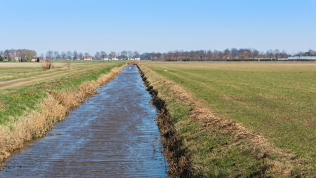 Ditch with a rippling water surface between two fields of grassland photo