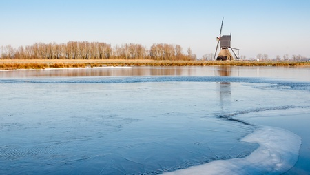 Dutch windmill beside a natural pond wih emerging ice  Stock Photo - 19265332