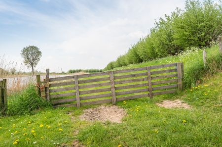 Angled wooden gate tied with rope in a rural area along a dike in springtime. photo