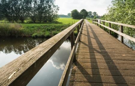 Houten brug over spiegelgladde water in een landelijk Nederlands landschap