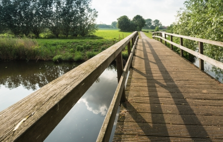 Wooden bridge over mirror smooth water in a rural Dutch landscape Stock Photo - 20403125