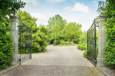 vintage mansion: View at a park with trees, grass and paths through an open black painted wrought iron gate.