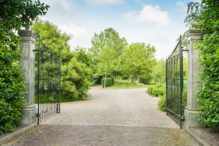 Voir dans un parc avec des arbres, de l'herbe et des chemins à travers une peinture porte en fer forgé noir ouvert. Banque d'images