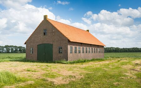 An old barn in a rural landscape with a blue sky with white clouds in summer. photo