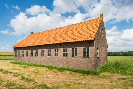 Old Dutch barn of brick masonry with an orange tile roof in the summer season. photo